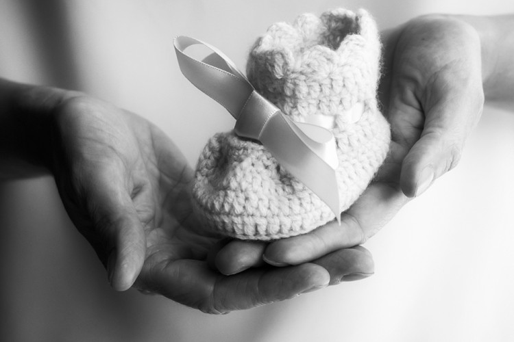 Sweet black and white image of two woman hands holding a newborn pink handmade baby bootie